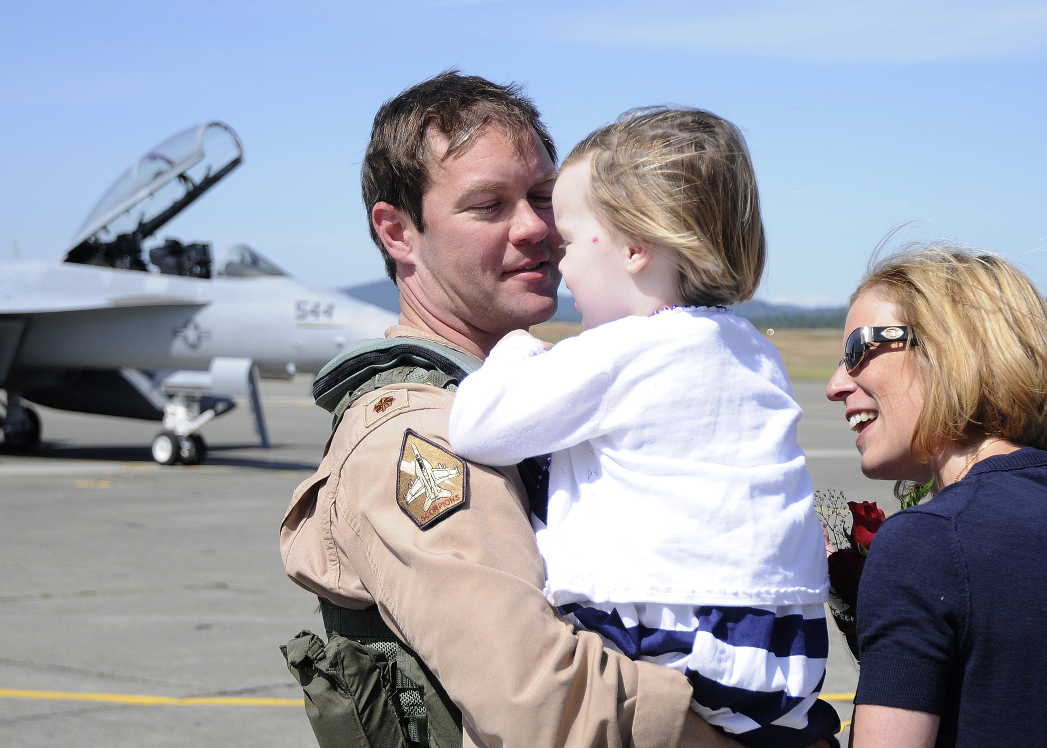 US Navy 110709-N-ZK021-011 Lt. Cmdr. Robert Scott is greeted by family during a homecoming ceremony at Naval Air Station Whidbey